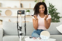 Beauty Blog. African American Female Blogger Reviewing Makeup Cosmetics Products Making Video Sitting On Sofa Near Camera At Home. Make-Up Blogging Concept. Selective Focus