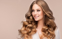 Beauty blonde girl with long  and   shiny wavy  hair .  Beautiful   woman model with curly hairstyle . Fashion, cosmetics and makeup