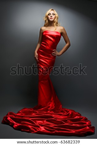 beauty blonde woman in red dress on gray background