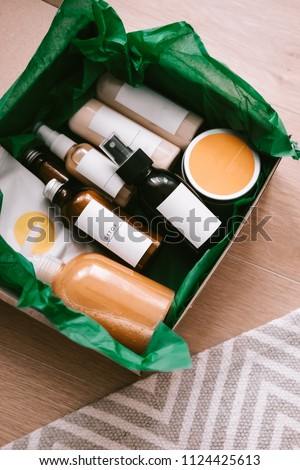 Beauty box with bottles of natural cosmetics, wrapped in green paper. Blogger hair and body care routine, salon treatments  #1124425613