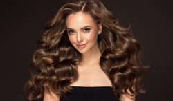 Beauty brunette  girl with long  and   shiny curly hair .  Beautiful  smiling woman model & wavy hairstyle . Care, treatment and spa