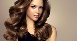 Beauty brunette girl with long  and   shiny wavy  hair .  Beautiful   woman model with curly hairstyle .