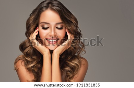 Beauty brunette girl with long shiny curly hair . Beautiful  smiling woman model  wavy hairstyle . Cosmetology, cosmetics and make-up.