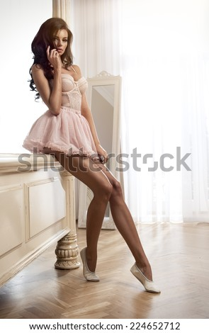 Beauty brunette woman in stylish room, wearing pink costume, ballet skirt and corset #224652712