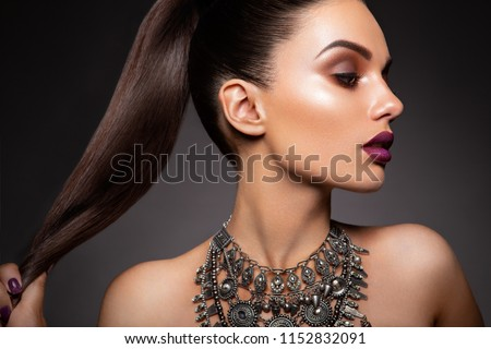 Stock Photo Beauty Brunette Woman with Perfect Makeup. Beautiful Professional Holiday Make-up. Red Lips, perfect eyebrows. Beauty Girl's Face isolated on dark background