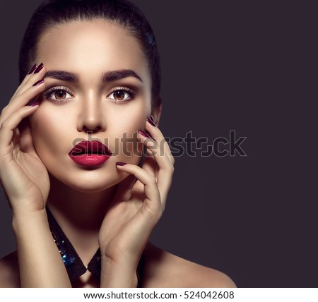 Beauty Brunette Woman with Perfect Makeup. Beautiful Professional Holiday Make-up. Red Lips and Nails, perfect eyebrows. Beauty Girl\'s Face isolated on dark background