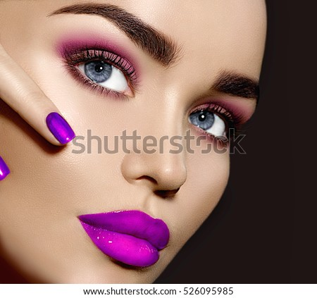 Beauty Brunette Woman with Perfect Makeup. Beautiful Professional Make-up. Red Lips and Nails, perfect eyebrows. Skin care, foundation, contouring. Beauty Girl\'s Face isolated on black background