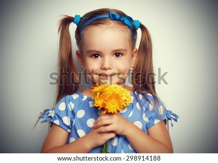 Beauty child girl in a blue dress with a bouquet of yellow flowers