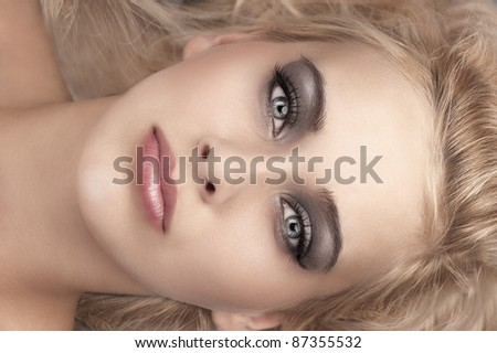 beauty close up portrait of a laying blonde with grey eyes, smokey eyes make up and soft pink glossy lips