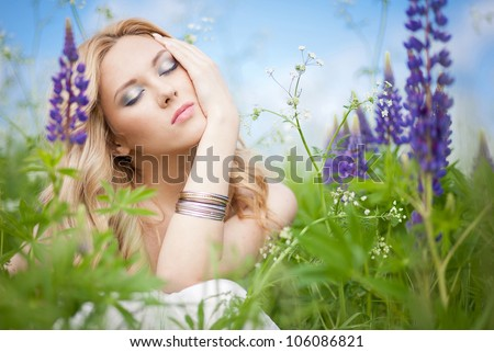 beauty close up portrait of a young pretty girl sitting in a field of flowers