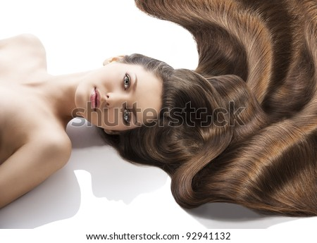 beauty close-up portrait of beautiful female face with long dark waved hairs laying down on the white. she is in front of the camera, looks in to the lens with happy expression #92941132