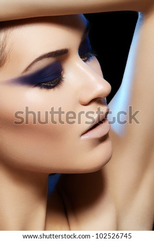 Beauty close-up portrait of beautiful sexy woman model with dark evening catwalk fashion eyes make-up and pale lips on gray background