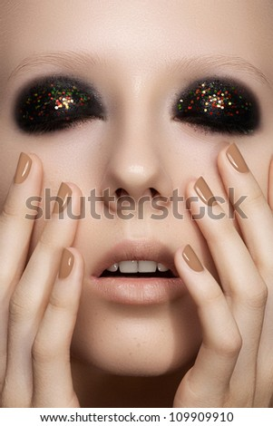 Beauty close-up portrait of sexy model woman with dark smoky eye make-up, bright glitter on eyelids, perfect beige nails polish. Cosmetics, makeup and manicure - stock photo