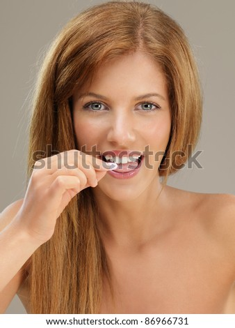 beauty closeup portrait of young, blonde woman, taking a pill