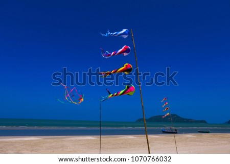 Beauty colorful kite or flag fly on the beach where it have white sand and blue sky on long holiday. Relaxation time  concept.