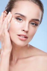 Beauty concept, beauty portrait of young woman applying cream under eyes. Head and shoulders of naturally beauty woman touching face under eyes, studio, dots of cream