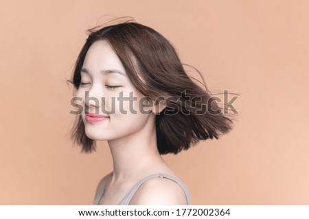 Beauty concept of an asian girl. Hair care. Skin care. Cosmetics. Yellow background.