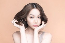 Beauty concept of an asian girl. Skin care. Cosmetics. Pale orange background.