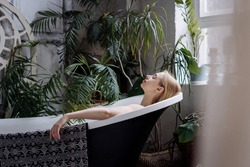 Beauty concept. Relaxed and serene young woman taking bath in boho chic apartment with cozy atmosphere. Dreamy female lying in tub, spending morning in bathroom with green house plants in pots