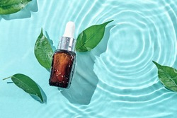 Beauty cosmetic lotion serum bottle and green leaves on water concentric circles background. Treatment skincare concept