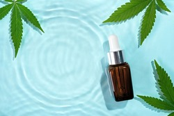 Beauty cosmetic lotion serum bottle and hemp leaves on water concentric circles background. Cosmetics CBD oil concept