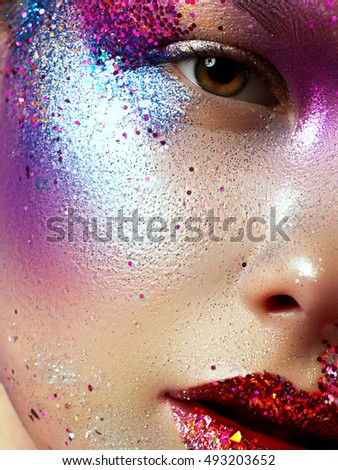 Beauty, cosmetics and makeup. Magic eyes look with bright creative make-up. Macro shot of beautiful woman\'s face with perfect art make up with glitter