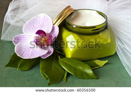 Beauty cream with orchid on green background