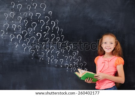 Beauty cute little ginger girl holding a book on the blackboard background