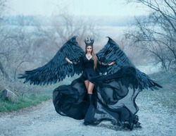 beauty dark goddess in wind, air flow waves silk long train black dress. fantasy model. queen with horns and black big wings ready to fly into sky. Cosplay character Maleficent. glamour autumn design