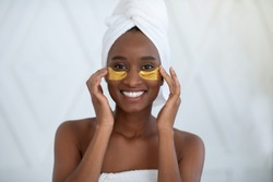 Beauty day and home skin care. Smiling young african american female with towel on head after shower applying golden patches under eyes to moisturize, in bedroom interior, white background, free space