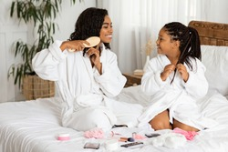 Beauty Day At Home. Black Mother And Daughter In Bathrobes Doing Hairstyles On Bed, Having Fun Together, Mom Combing Hair And Little Daughter Touching Braids, Different Makeup Cosmetics Lying Around