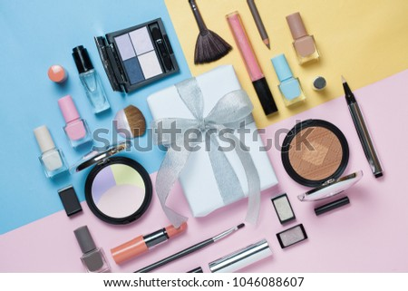 Beauty, decorative cosmetics and gift box with bow. Makeup brushes set and color eyeshadow palette on bright multicolor and blue background , flat lay, top view, Minimalistic style