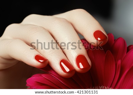 Beauty delicate hands with manicure holding pink flower  close up. Beautiful nails and flower close-up, great idea for the advertising of cosmetics.