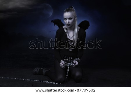Beauty devil girl in a chains over dark sea background