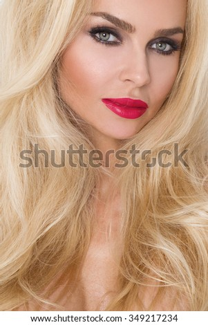 Beauty face of the young beautiful woman - isolated on white background. Gorgeous female portrait with slicked blond hair. Young adult girl with healthy skin. Pretty lady with fashion eye makeup.