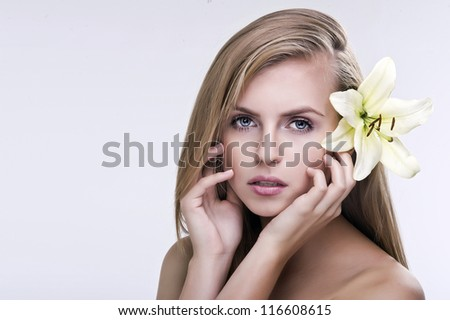 Beauty face of the young beautiful woman with flower. Female tou