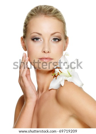Beauty face of the young beautiful woman with flower. Female touching skin. Girl on white background