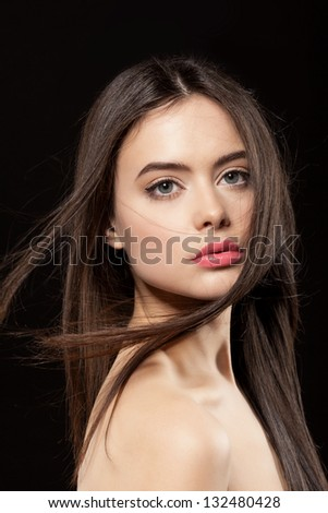 Beauty face of woman with clean fresh skin and long hair on dark background