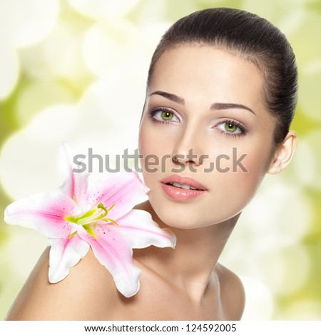 Beauty face of young woman with flower. Beauty treatment concept. Blinking Background. Bokeh