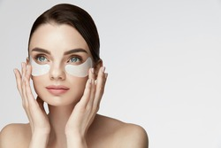 Beauty Face Skin Care. Closeup Of Young Woman With Beautiful Big Eyes, Natural Makeup And Fresh Facial Skin Applying Under-eye Patches On Face. High Resolution
