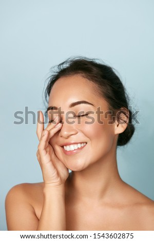 Beauty face. Smiling asian woman touching healthy skin portrait. Beautiful happy girl model with fresh glowing hydrated facial skin and natural makeup on blue background at studio. Skin care concept