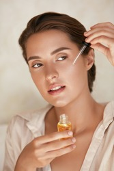 Beauty Face. Woman Applying Essential Oil On Facial Skin And Looking Away. Beautiful Model Moisturizing Derma With Natural Vitamin E, Serum Collagen And Hyaluronic Acid.