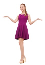 beauty, fashion, advertisement and happy people concept - young woman in purple dress and high heels holding something on palm of her hands