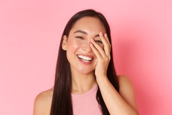 Beauty, fashion and lifestyle concept. Close-up of carefree beautiful asian woman touching face and laughing happily with closed eyes, standing over pink background joyful, skincare product promo