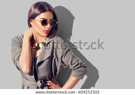 Beauty Fashion brunette model girl wearing stylish coat and sunglasses. Sexy woman portrait with perfect makeup, trendy accessories and fashion wear. Beauty trends. Isolated on grey. Fashion blogger