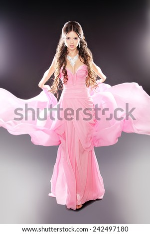 Beauty fashion girl model posing in pink blowing transparent chiffon dress over dark lights background. Diamond Jewelry.