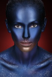 Beauty fashion Girl with colorful make-up, blue Paint on Skin. Halloween Alien Makeup. Creative visage.