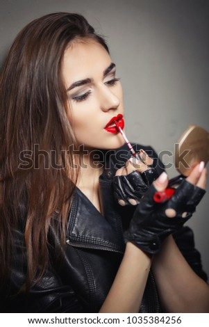 Beauty fashion glamour girl colors the lips. Biker`s style girl wearing gloves. Sexy red lips. Portrait of super stylish, fashionable beautiful young woman brunette wearing leather jacket and gloves. #1035384256