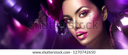 Beauty fashion model girl creative art makeup, over purple, pink and violet air balloons background. Woman face Make-up with gems, pink with gold lips, purple eyeshadows. Widescreen