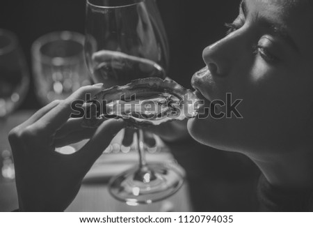 Beauty Fashion model girl. Fashion look. girl or woman eating oyster with wine in luxury restaurant. woman or girl eating oyster in hand and drink red wine.
